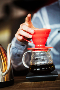 Specialist coffee shop. A man brewing coffee using a filter paper, and drinking it.の写真素材 [FYI02253538]