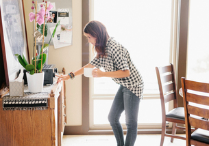 Woman with long brown hair, wearing a chequered shirt and jeans, holding a mug, switching on stereo.の写真素材 [FYI02253552]