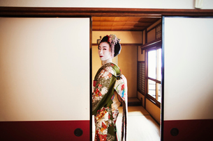 A woman dressed in the traditional geisha style, wearing a kimono and obi, with an elaborate hairstyの写真素材 [FYI02253569]