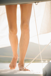 Teenage girl standing barefoot on a sail boat.の写真素材 [FYI02253575]