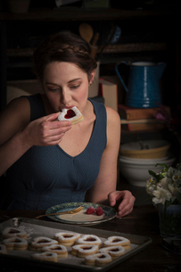 Valentine's Day baking, young woman sitting in a kitchen, eating a heart shaped biscuit.の写真素材 [FYI02253576]