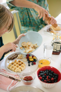 Boy sitting at breakfast table, waffles, fruit and juice.の写真素材 [FYI02253579]