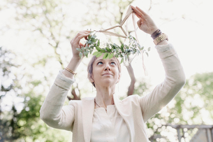 Woman standing in a garden, putting a flower wreath in her hair.の写真素材 [FYI02253610]