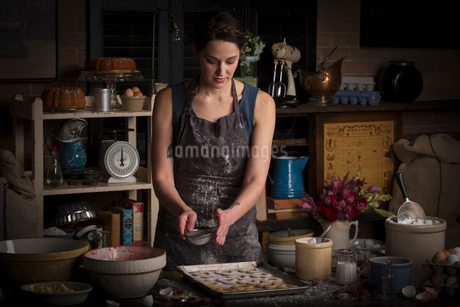 Valentine's Day baking, young woman standing in a kitchen, sprinkling icing sugar over heart shapedの写真素材 [FYI02253620]