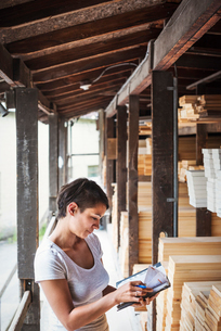 Woman standing in a lumber yard, holding a folder, checking notes.の写真素材 [FYI02253622]
