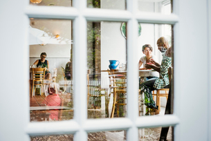 View through a window into a cafe, people sitting at tables.の写真素材 [FYI02253675]