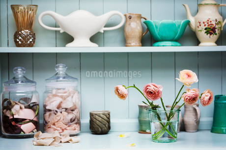 A shelf with vases and ceramic pots, and flowers in a vase.の写真素材 [FYI02253677]