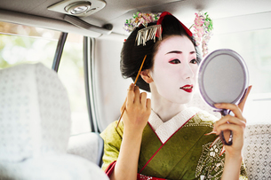 A woman dressed in the traditional geisha style, wearing a kimono and obi, with an elaborate hairstyの写真素材 [FYI02253678]