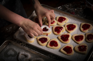 Valentine's Day baking, woman spreading raspberry jam on heart shaped biscuits.の写真素材 [FYI02253680]