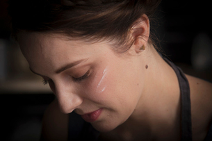 Valentine's Day baking, close up portrait of a young woman with flour on her cheek.の写真素材 [FYI02253686]