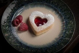 Valentine's Day baking, high angle view of a plate with heart shaped biscuits and fresh raspberries.の写真素材 [FYI02253694]