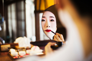 Geisha woman with traditional white face makeup applying bright red lipstick with a brush looking inの写真素材 [FYI02253698]