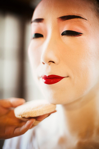 A modern woman creating the traditional geisha vivid red lips by painting on lipstick with a fine brの写真素材 [FYI02253706]