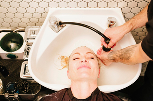 A female client at a hair salon, having her hair rinsed in a basin.の写真素材 [FYI02253714]