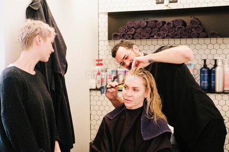 A hair stylist cutting a woman's hair in a hair salon.の写真素材 [FYI02253717]