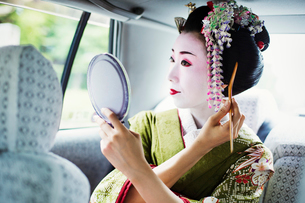 A woman dressed in the traditional geisha style, wearing a kimono and obi, with an elaborate hairstyの写真素材 [FYI02253730]