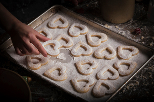 Valentine's Day baking, woman arranging heart shaped biscuits on a baking tray.の写真素材 [FYI02253742]
