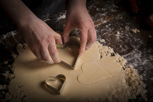 Valentine's Day baking, woman cutting out heart shaped biscuits from dough.の写真素材 [FYI02253748]