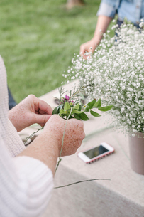 Close up of a woman, standing in a garden, making a flower wreath.の写真素材 [FYI02253751]