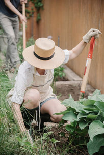 A woman in a wide brimmed straw hat working in a garden, digging.の写真素材 [FYI02253775]