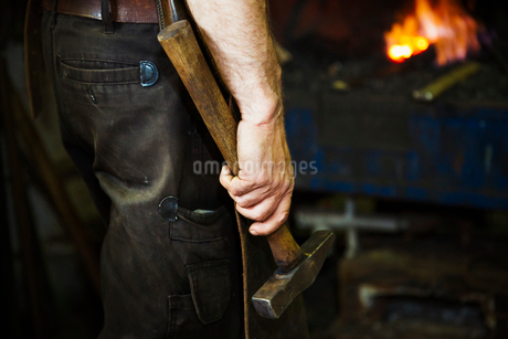 A man in a leather apron holding a hammer in a workshop.の写真素材 [FYI02253786]