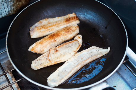 Close up of fish fillets being fried in a frying pan.の写真素材 [FYI02253791]