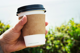 Close up of a human hand holding a disposable paper cup with a cardboard sleeve and plastic lid.の写真素材 [FYI02253802]
