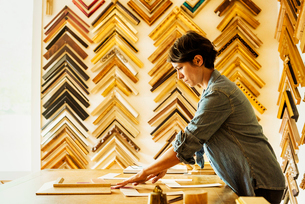 Woman working at a picture framers, a large selection of frames on the walls.の写真素材 [FYI02253851]