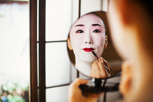 Geisha woman with traditional white face makeup applying bright red lipstick with a brush, using a mの写真素材 [FYI02253858]