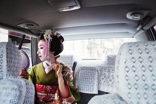 A woman dressed in the traditional geisha style, wearing a kimono with an elaborate hairstyle and flの写真素材 [FYI02253862]