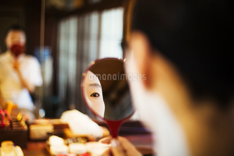 A modern geisha or maiko woman being prepared in traditional fashion, with white face makeup.の写真素材 [FYI02253872]