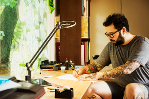 Bearded man with tattoos wearing glasses, sitting at a desk, drawing.の写真素材 [FYI02253874]