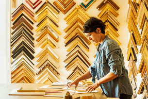 Woman working at a picture framers, a large selection of frames on the walls.の写真素材 [FYI02253876]