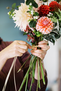 Organic flower arrangements. A woman creating a hand tied bouquet.の写真素材 [FYI02253878]