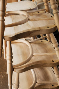 Close up of a stack of wooden chairs in a carpentry workshop.の写真素材 [FYI02253893]