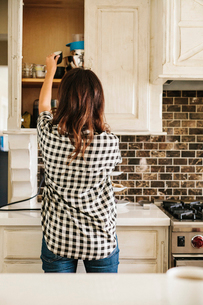 Rear view of  woman with long brown hair, wearing a chequered shirt, standing in a kitchen.の写真素材 [FYI02253898]