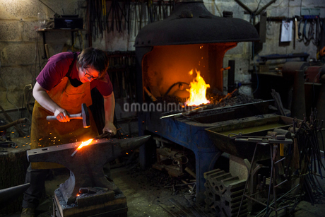 A blacksmith striking red hot metal on an anvil inside a workshop.の写真素材 [FYI02253915]