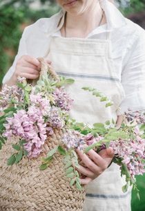 A woman holding a basket of cut branches with pink flowers.の写真素材 [FYI02253931]