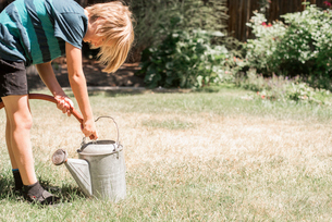 Blond boy standing in a garden, filling a watering can from a garden hose.の写真素材 [FYI02253934]