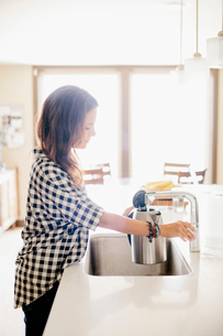 Woman with long brown hair, wearing a chequered shirt, standing at a kitchen sink.の写真素材 [FYI02253942]