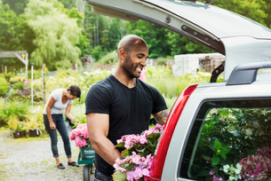 Car parked at a garden centre, a man loading flowers into the boot.の写真素材 [FYI02253944]