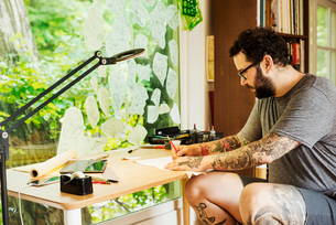 Bearded man with tattoos on his arms and legs sitting at a desk, drawing.の写真素材 [FYI02253948]