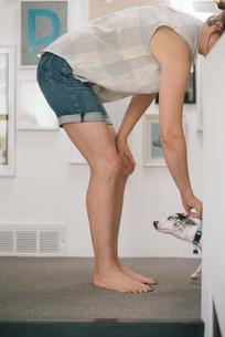 Barefoot woman wearing denim shorts standing indoors, stroking white dog.の写真素材 [FYI02253959]