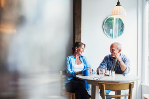 Two people seated at a coffee shop table.  Blurred foreground.の写真素材 [FYI02253964]