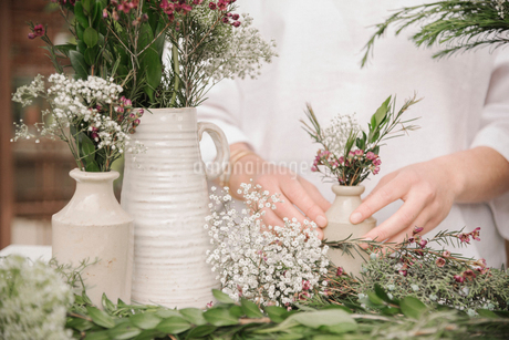 a woman preparing a mixture of herbs for cooking, stripping the leaves off for chopping.の写真素材 [FYI02253966]
