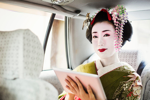 A woman dressed in the traditional geisha style, wearing a kimono with an elaborate hairstyle and flの写真素材 [FYI02253969]