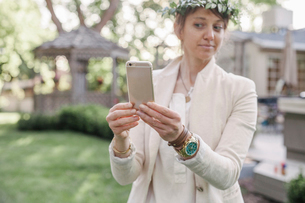 Woman with a flower wreath in her hair, standing in a garden, taking a selfie with her mobile phone.の写真素材 [FYI02253972]