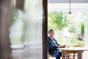 A man seated at a table looking at a smart phone.  Blurred foreground.の写真素材 [FYI02253973]