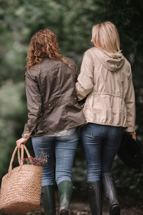 Two women arm in arm walking in coats and boots along a country path with a basket.の写真素材 [FYI02253980]