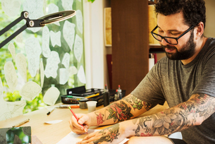 Bearded man with tattoos on his arms, sitting at a desk, drawing.の写真素材 [FYI02253987]